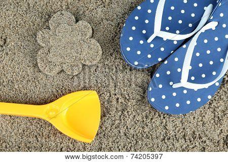 Flower-shaped wet sand and flip flops, close-up