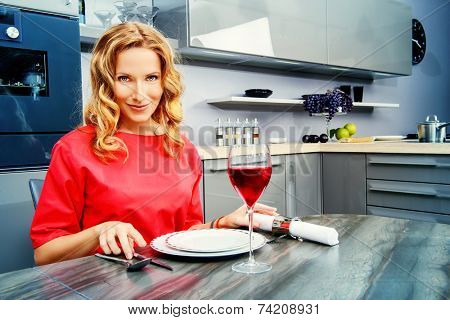 Beautiful elegant woman having a dinner at a kitchen at home. Home interior.