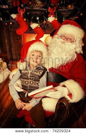 Santa Claus in his everyday clothes in Christmas home decoration. Happy little boy helps Santa Claus get ready for Christmas.
