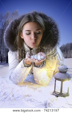 Girl on a winter glade blows on snowflakes. Woman with a lantern
