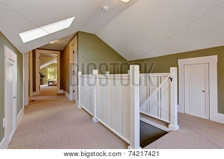 Green And White Upstairs Hallway With Vaulted Ceiling And Skylight
