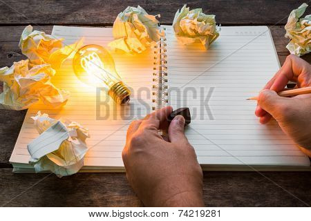 Hand write over Note book and light bulb on wood table