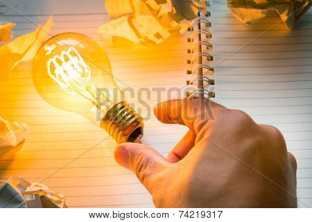Hand pick light bulb over  Note book on wood table