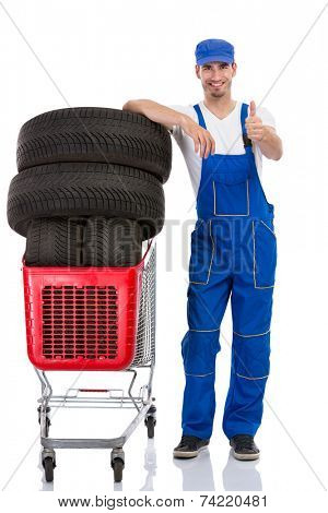 Young mechanic with tyre giving a thumbs up