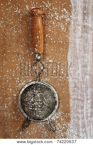 Vintage sieve on parchment paper with distressed wood as background.  Baking concept.