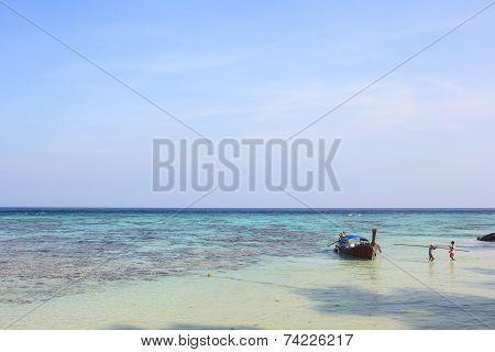 LIPE ISLAND, SATUN, THAILAND - SEP29, 2014: Fisherman Sailed Longtail Boat On The Beach
