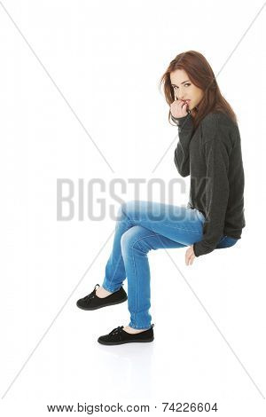 Young stressed woman biting her nails