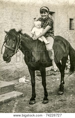 POLAND, CIRCA SIXTIES: Vintage photo of mother and baby daughter sitting on horse