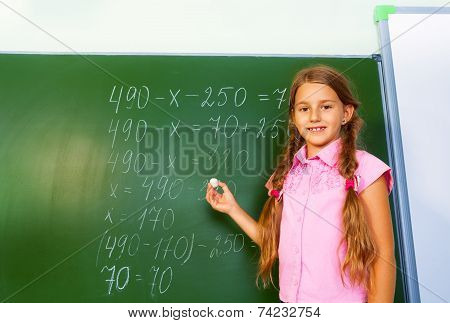 Girl with braids and chalk in hand near blackboard