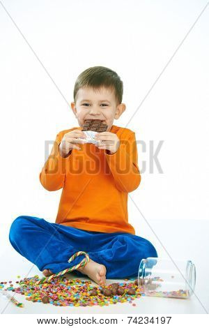 Joyous little kid eating chocolate sitting cross-legged on floor, sweets spilt. Isolated on white.