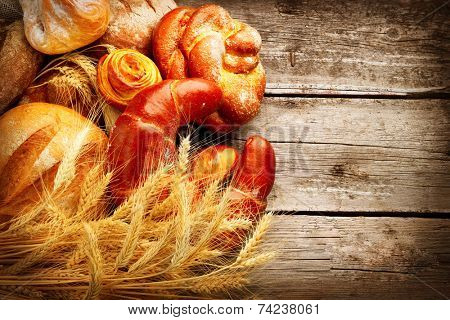 Bakery Bread on a Wooden Table. Various Bread and Sheaf of Wheat Ears over Wood Background