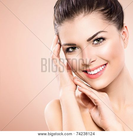Beauty Portrait. Beautiful Spa Girl Touching her Face. Perfect Fresh Skin. Pure Beauty Model Girl. Youth and Skin Care Concept. Beauty Teenage Model Girl Portrait over pink background