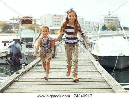 Two fashion kid girls wearing navy clothes in marine style walking in the sea port