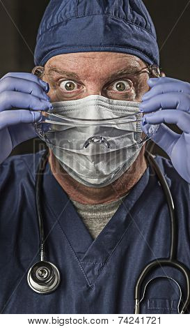 Determined Looking Male Doctor or Nurse with Protective Wear and Stethoscope.