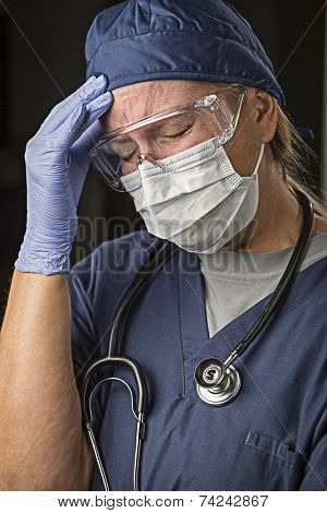 Grimacing Female Doctor or Nurse Wearing Protective Facial Wear and Surgical Gloves.