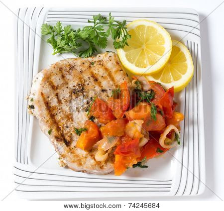 Marlin steak grilled and served with a tomato onion salsa viewed from above