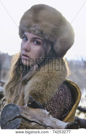 portrait photo of blond hair wind girl looking to camera wearing fur hat in early spring