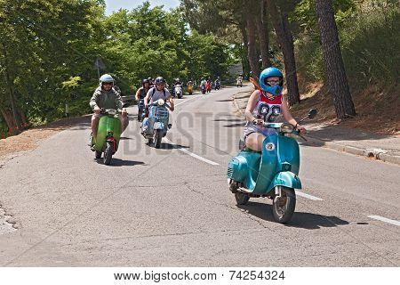 Girl Leads A Group Of Bikers Riding A Vintage Italian Scooter