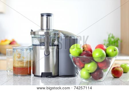 Apple juice on juicer machine - juicing concept. Apples in bowl in kitchen and fresh pressed juice.