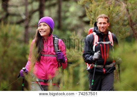 Hiking people - hikers trekking in forest on hike. Couple on adventure trek in beautiful forest nature. Multicultural Asian woman and Caucasian man living healthy active lifestyle in woods.
