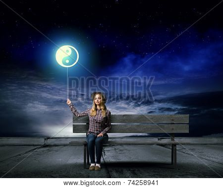 Young woman sitting on bench with balloon in hand