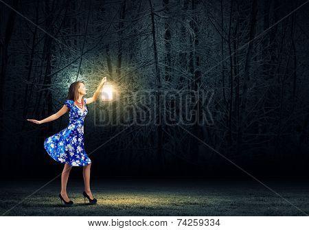 Young woman in blue dress walking in night wood