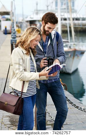 tourist couple with guide book on vacation