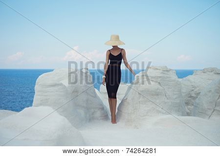 Fashion photo of beautiful lady in hat in an unusual landscape