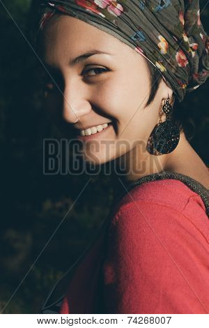 Natural outdoor portrait of a stylish woman wearing a headscarf turning to look over her shoulder at the camera with a friendly smile