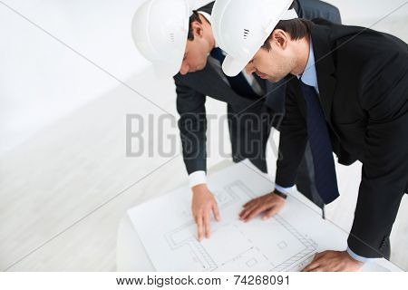 Two businessmen in helmets indoors