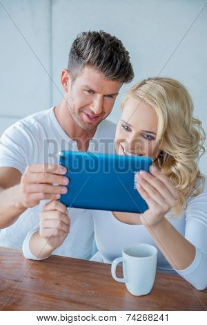Couple smiling as they read a tablet computer together while they enjoy their morning coffee catching up on social media and morning news