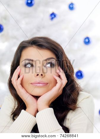 Thoughtful young woman in front of a Christmas tree decorated with blue baubles looking to the side with her chin resting on her hands