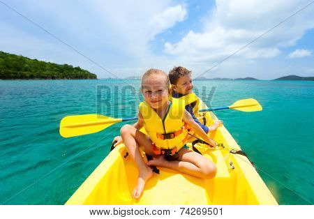 Kids enjoying paddling in colorful yellow kayak at tropical ocean water during summer vacation