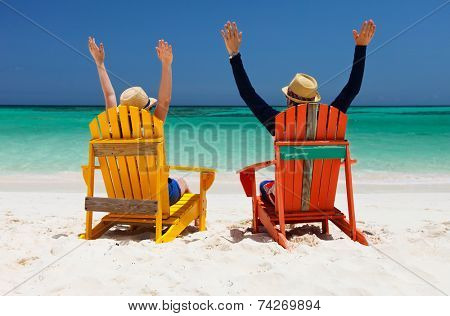 Happy couple sitting on colorful chairs at tropical beach enjoying Caribbean vacation