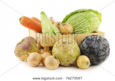 collection of fresh winter vegetables in a wooden crate on a white background