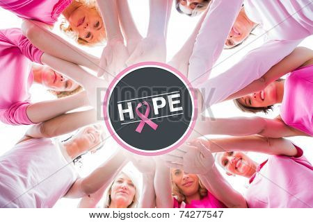 Diverse women smiling in circle wearing pink for breast cancer against breast cancer awareness message on poster