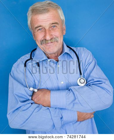 Portrait of a senior doctor on blue medical background