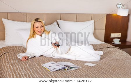Woman Lying On Bed Watching Tv