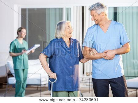 Happy male nurse assisting senior woman to walk with caretaker in background at nursing home yard