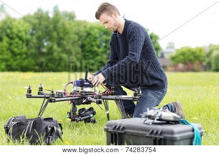 Young engineer preparing surveillance drone in park