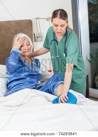 Female caretaker using hot water bottle on senior woman's leg at nursing home