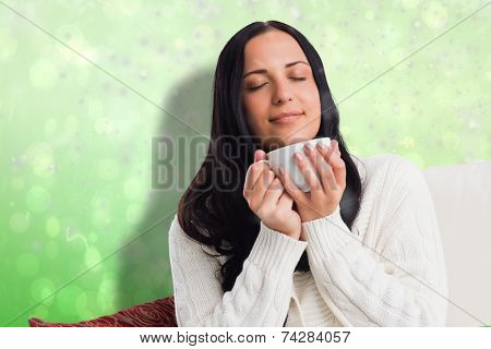 Woman enjoying a lovely drink against green abstract light spot design