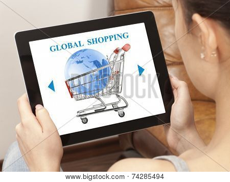 Woman using laptop with online global shopping cart on screen