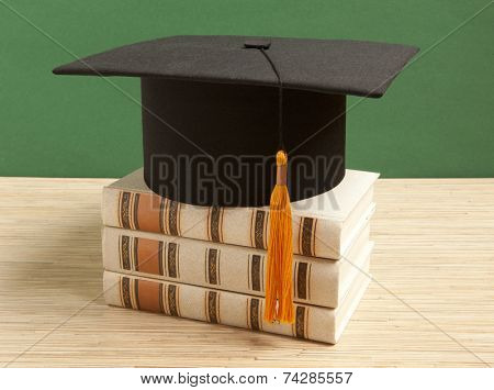 Graduation hat with old book on the background of school board