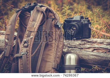 Lifestyle hiking camping equipment retro photo camera backpack and thermos outdoor