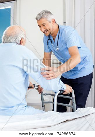 Male caretaker assisting senior man to use walking frame in bedroom at nursing home