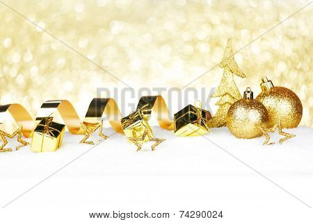 Beautiful various golden christmas decor on snow close-up