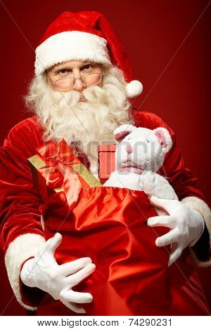 Portrait of generous Santa Claus holding presents in big red sack