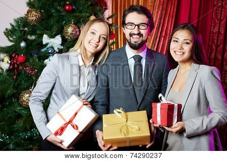 Portrait of joyful colleagues with giftboxes standing by xmas tree