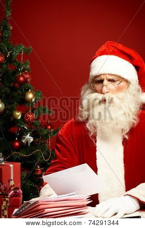 Santa Claus reading wish letter and frowning